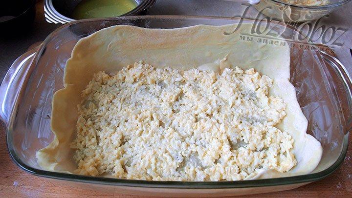 На первый слой пирога кладем тертый сыр