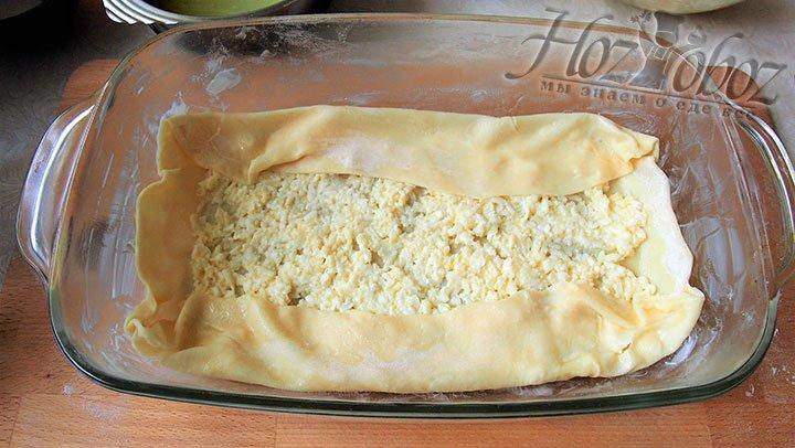 Высокие края теста заворачиваем на слой сыра