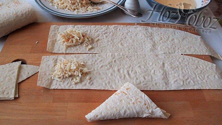 Чтобы сформировать треугольники, в самом начале полосы из лаваша выложим сыр