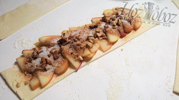 На полосу теста выкладываем яблоки, орехи и корицу с сахаром, при этом края оставляем пустыми