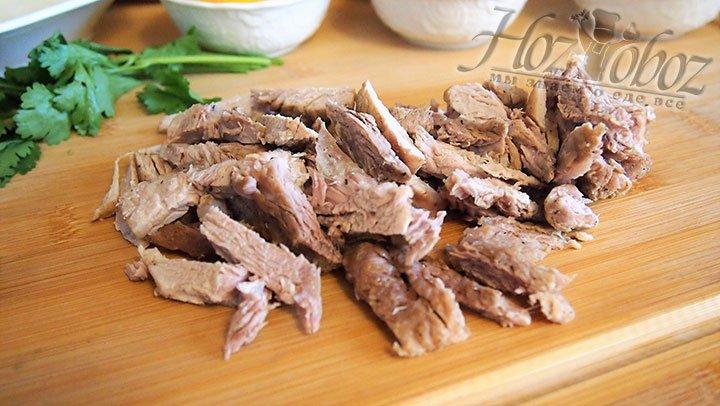 Предварительно обжаренное мясо нарезаем длинными полосками
