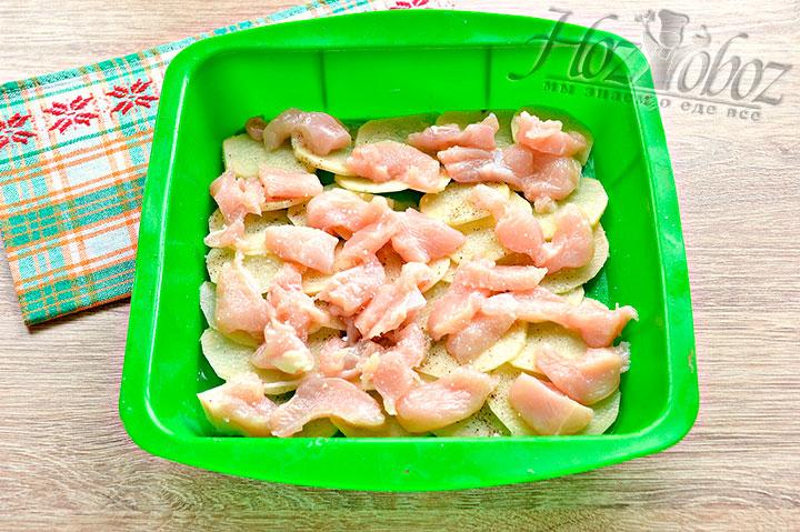 Нарезаем куриное мясо, помещаем кусочки на картофель, солим