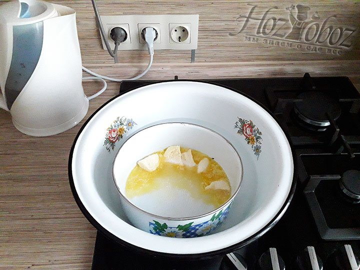 В другую миску нарезаем кусочками масло и добавляем оставшийся сахарный песок, а затем помещаем на водяную баню