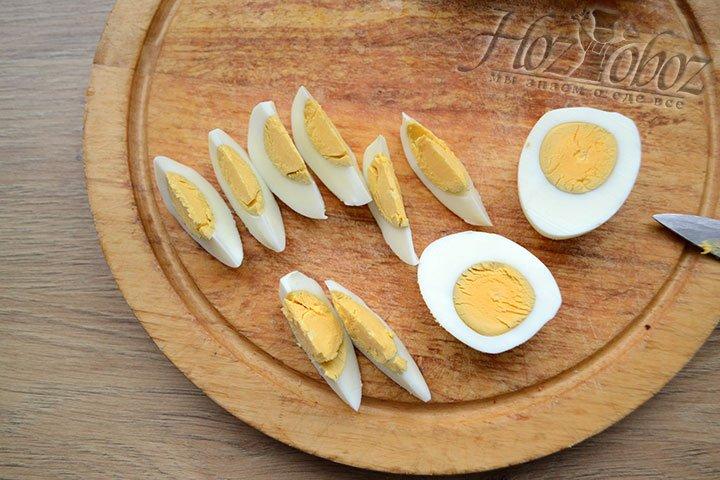 Уже очищенные яйца разрезаем пополам, а затем дольками. Каждой яйцо следует разделить на 8 долек