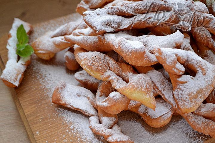 Готовый хворост подаем к столу на доске и декорируем для аромата листьями свежей мяты с медом или джемом