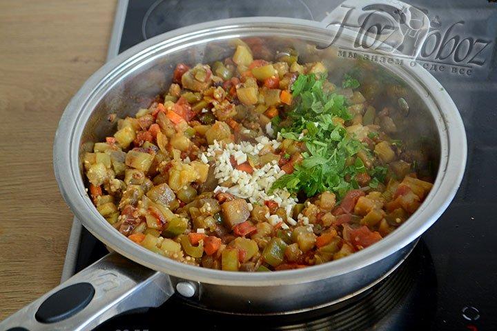 Добавляем чеснок и овощи к баклажанам, перемешаем и даем слегка остыть под крышкой.