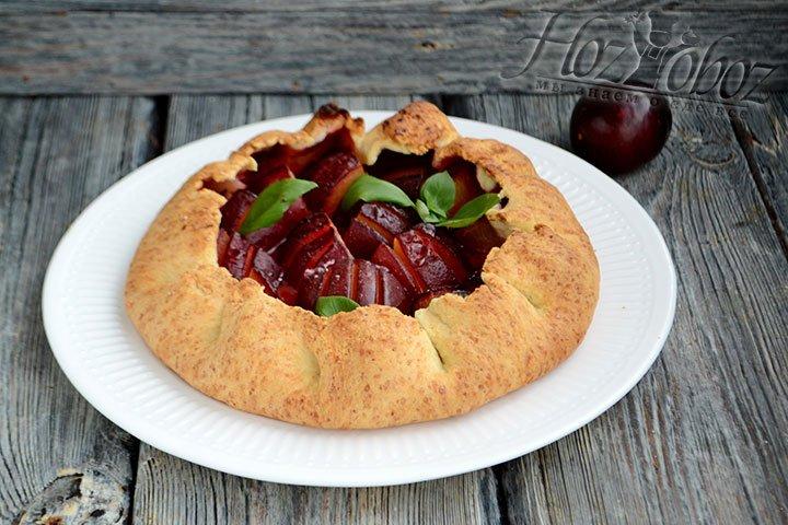 Перекладываем сливовый пирог на блюдо и украшаем свежим базиликом.