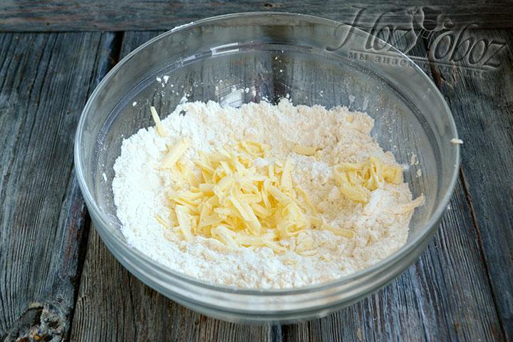 Сливочное масло натираем в глубокую миску с сухими ингредиентами. Перетираем в песочную крошку.