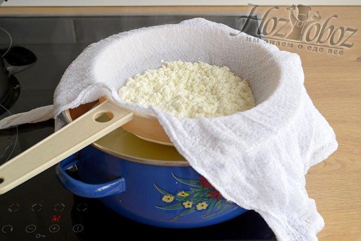 В сито, застеленное марлей, сливаем получившиеся хлопья сыра. Отделяем их от молочной сыворотки.