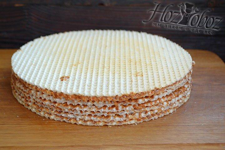 Чередуя вафли и крем, формируем торт. Сверху на 20 минут кладем груд, чтобы вафли прижались друг к другу.