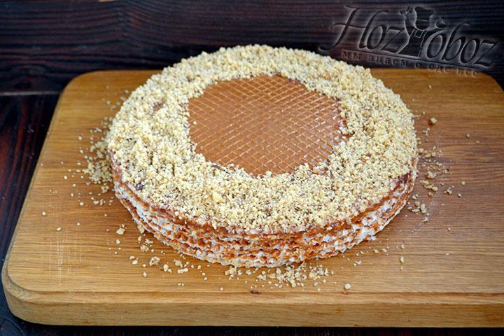 Украшаем торт грецкими орехами, обсыпав ними край верхнего коржа.