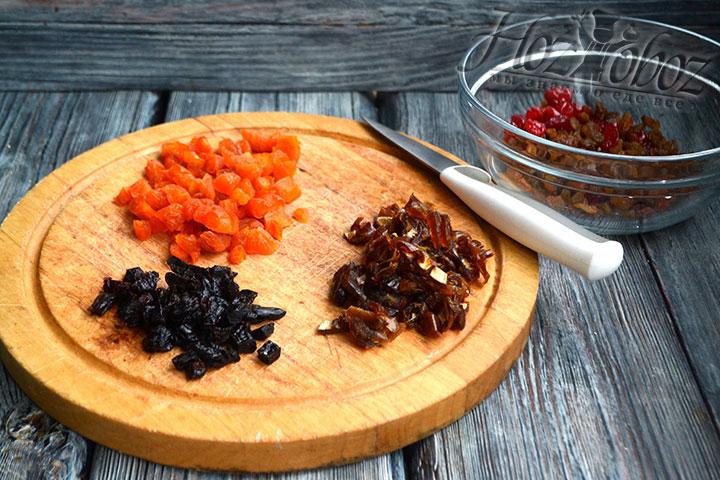 В миске соединяем нарезанные курагу, чернослив и финики, а также вишню и изюм.