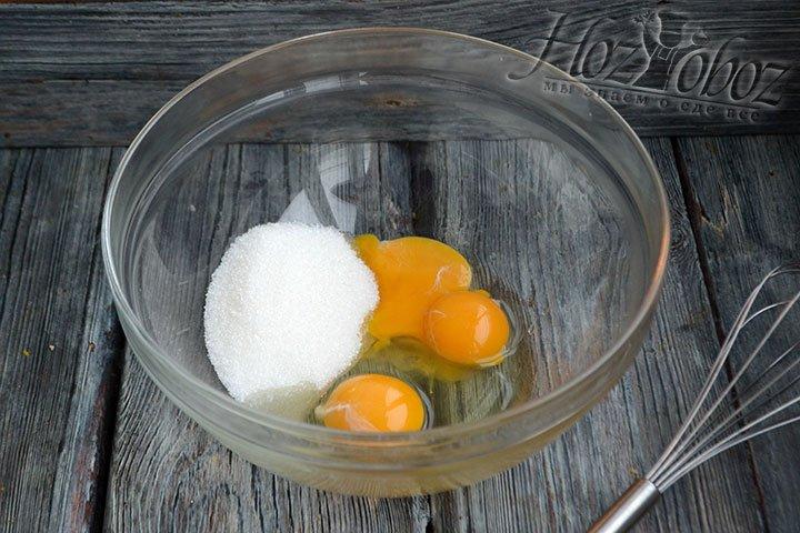 Сахар соединяем с куриным яйцом и двумя желтками.