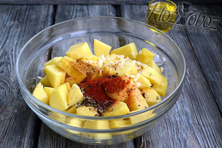 Картофель соединяем в глубокой миске со специями и чесноком.