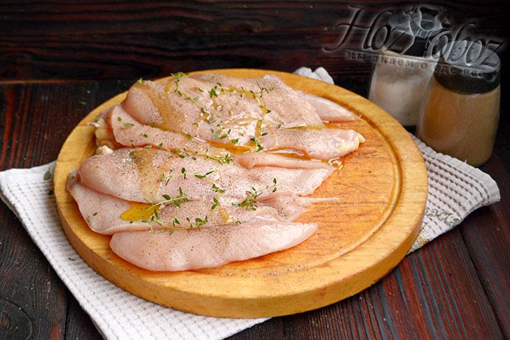 Куриное филе разрезаем вдоль на две части, добавляем соль и специи, а также оливковое масло и зелень тимьяна.