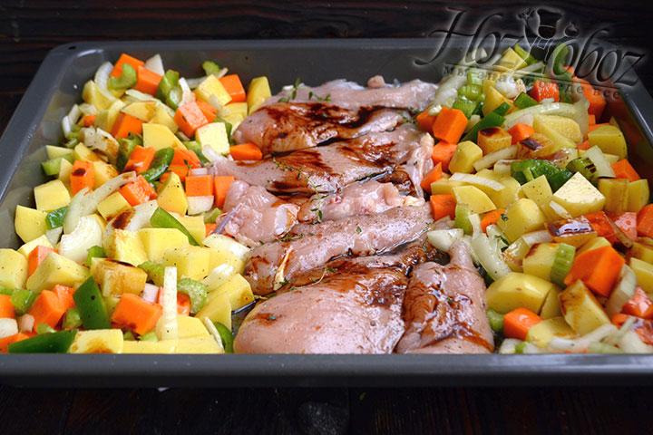 В форму для запекания перекладываем овощи, солим, перчим и поливаем оливковым маслом. Перемешиваем ингредиенты. В центр выкладываем подготовленные кусочки куриного филе.