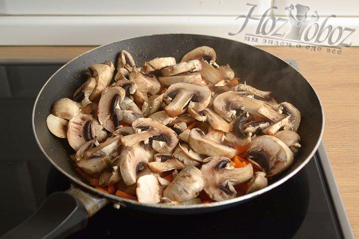 Добавьте нарезанные пластинами шампиньоны в сковороду к овощам и обжаривайте еще 5-7 минут.
