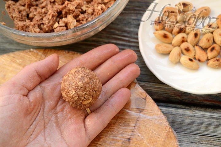 Катаем шарик между ладонями, пока масса не будет плотно держать орешек внутри.
