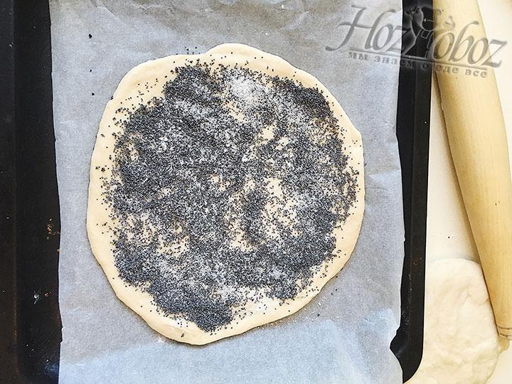 Тем временем, включаем духовку разогреваться, устанавливаем температуру на 190 градусов. Противень для выпекания застилаем пергаментом, на него выкладываем один пласт теста, посыпаем тесто смесью мака и двумя столовыми ложками сахарного песка, сверху высыпаем ванилин.