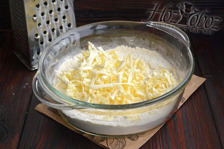 Сливочное масло после морозильной камеры натираем в миску с мукой и разрыхлителем.