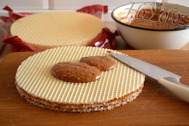 Собираем торт – выкладываем на ровную поверхность корж, а на него – несколько ложек крема.
