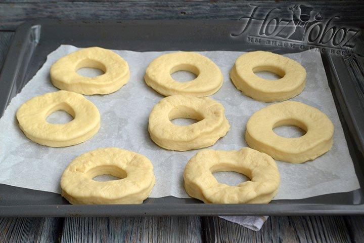 Складываем заготовки пончиков на противне, застеленном пергаментом. Еще 20 минут им нужно для роста.