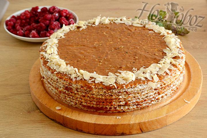 Достаем торт из холодильника, наносим крем и украшаем края торта миндальными лепестками.